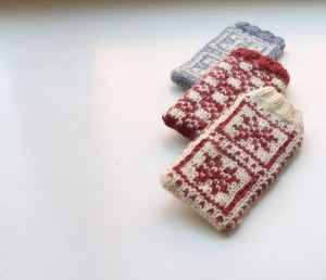 "Three different varieties of smart phone cosies. The outer two are based on the pattern in ""knit Nordic"". The middle one is a new pattern."